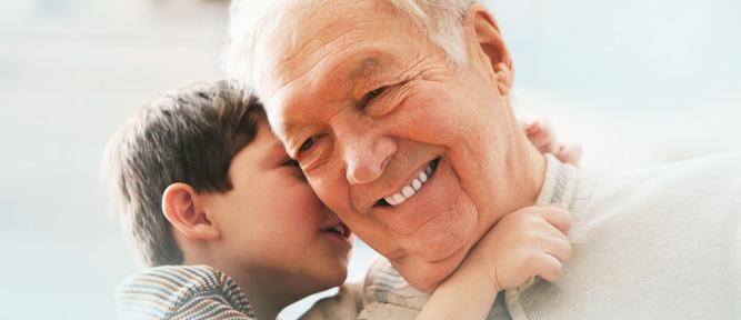 boy whispering in older man's ear